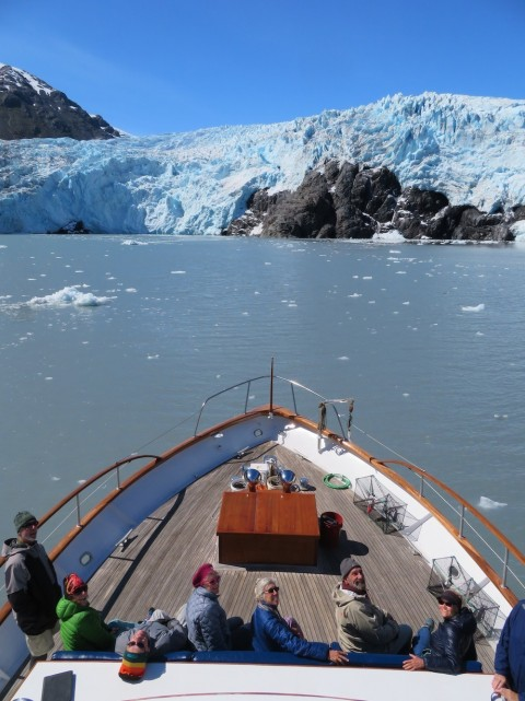 Passengers aboard the M/V Sea Star powered by luxury yacht company North Pacific Expeditions linger in front of a tidewater glacier