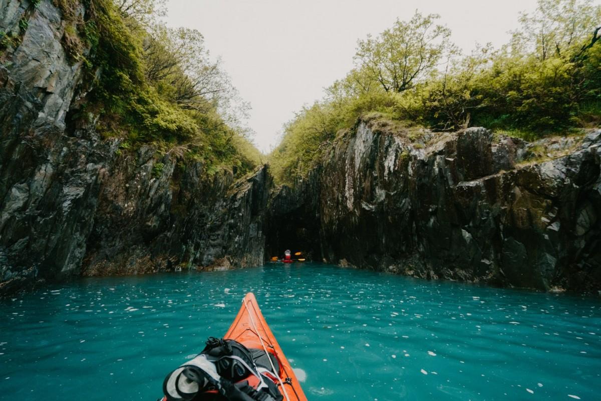 Kayaker paddles close to shore in Kenai Fjords National Park