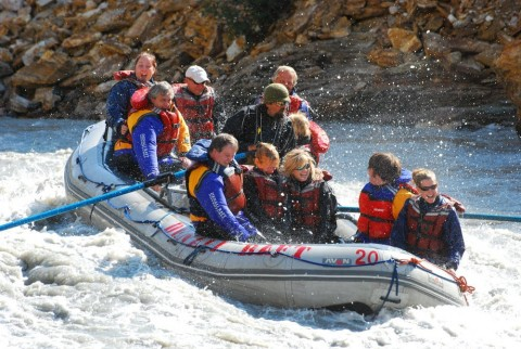 A group of people float down a choppy river on a raft
