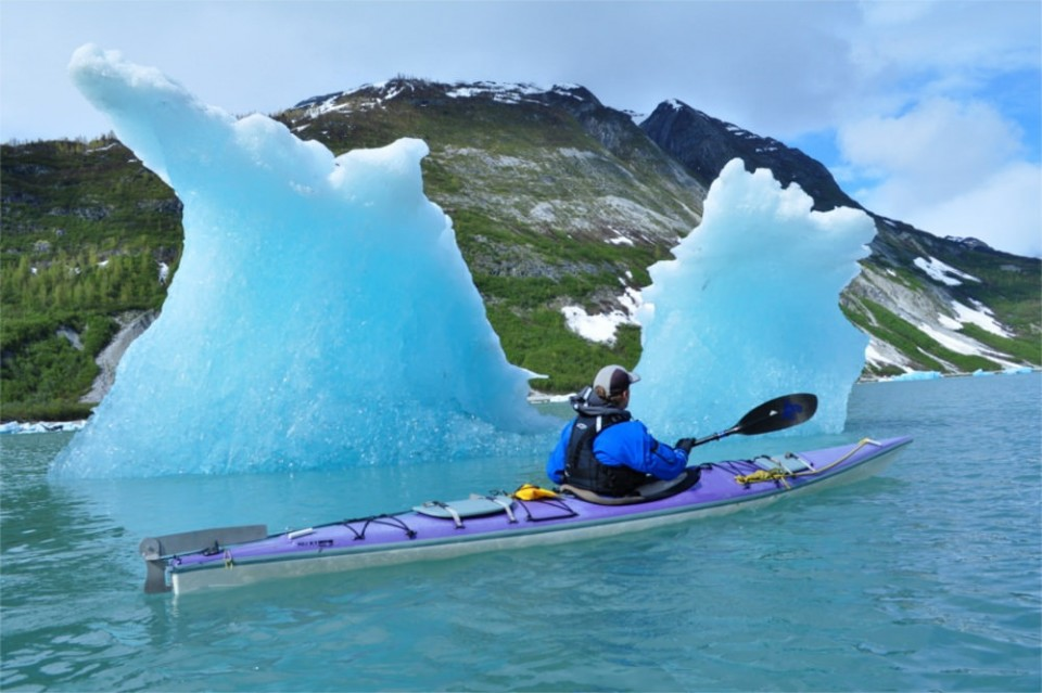 A guest with Alaska Mountain Guides kayaks past an ice berg.