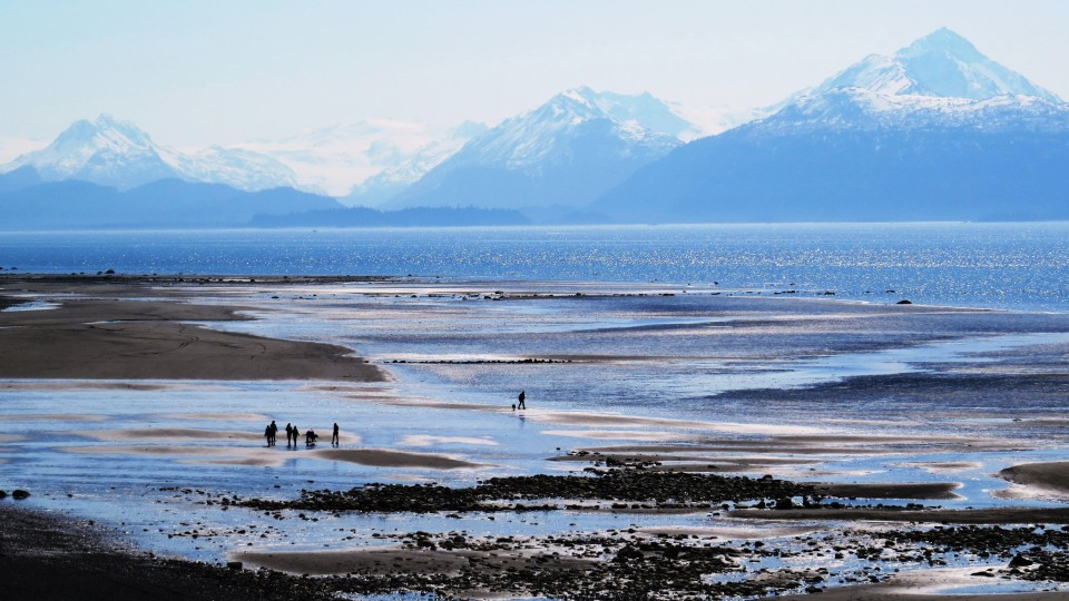 A few people stroll along Bishop's Beach with mountains in the background.