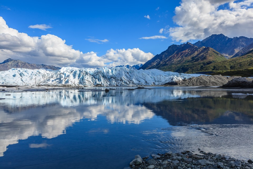 Matanuska Glacier with mountains in the background reflected on the water.