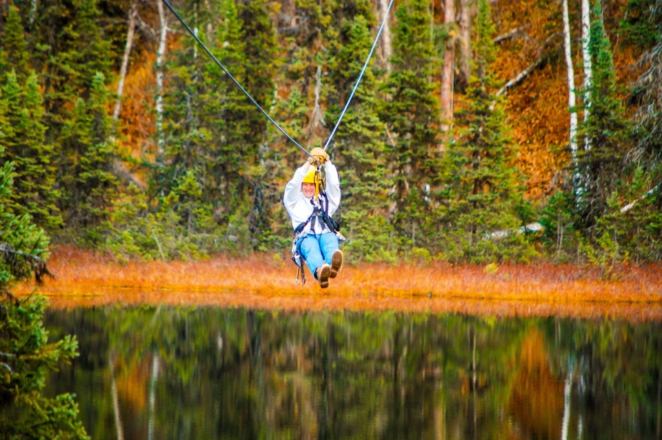 A woman rushes through the air over a lake on a zipline in an Alaska autumn forest setting.
