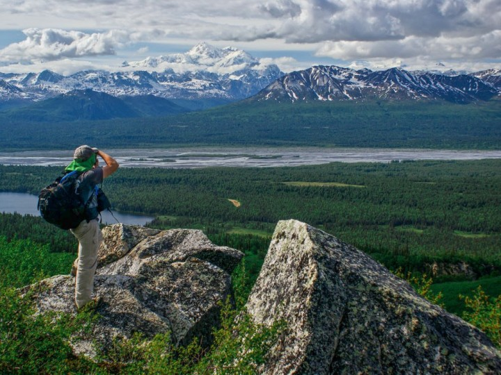 A hike takes a picture of a Alaskan river with mountains in the background.
