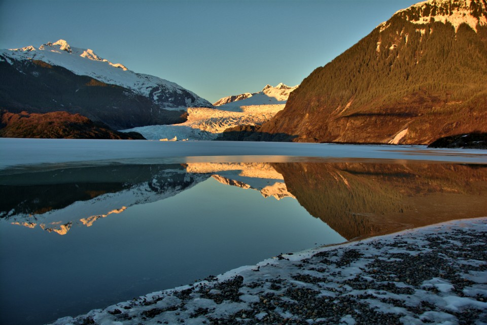 Mendenhall Glacier with an alpine glow and reflecting on the water