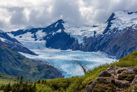 Portage Glacier surrounded by lush greenery and blue mountains.