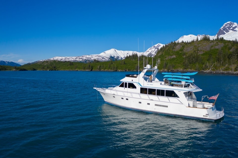 A luxury yacht sails along Prince William Sound with snow capped mountains in the background.