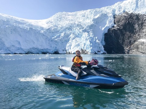 A smiling woman on a jet ski in front of a glacier.