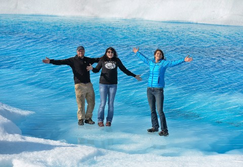 Three people pose with arms outstretched while they stand on the vibrant blue Knik Glacier.