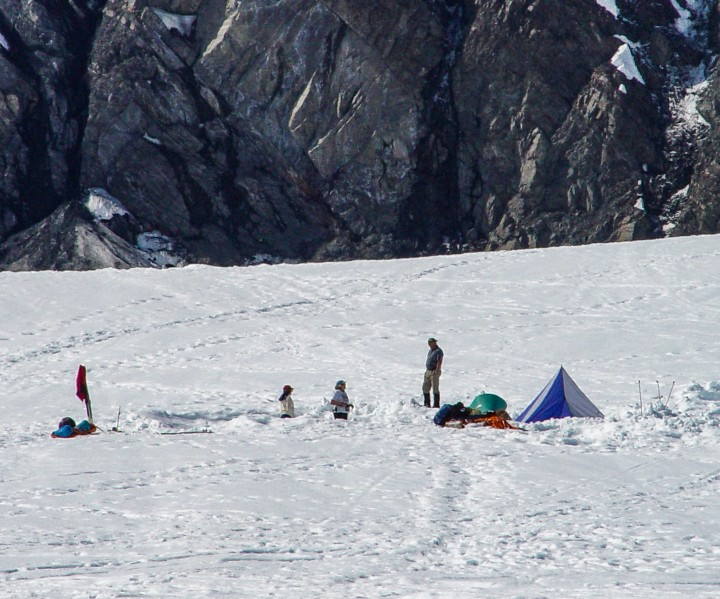 Hikers camp and explore on the snow with the Denali mountainside in the background.