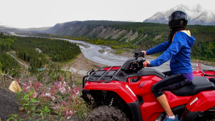 A woman on a red ATV overlooks an Alaskan valley with a river running through it.