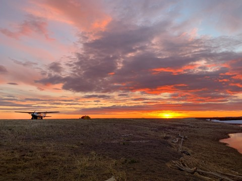 A landed bush plane sits in front of a stunning golden sunset.