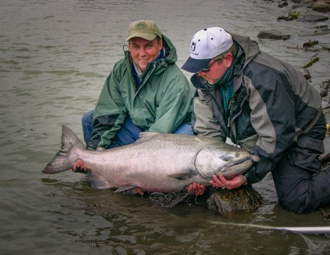 Two people kneel in the water to hold a large fish they caught.