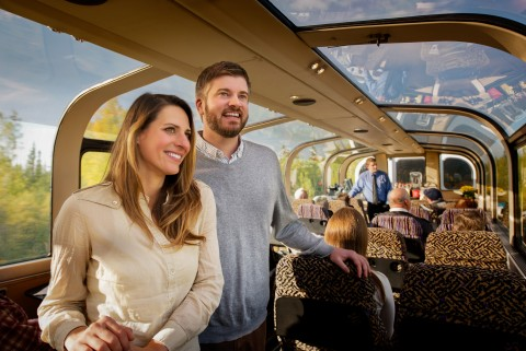 A couple enjoys looking out the windows of a train.