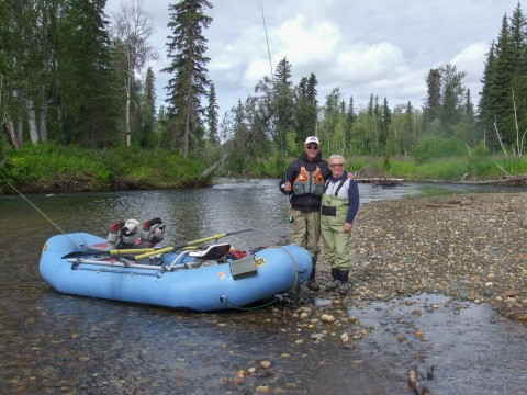 A couple in waders holding fishing poles poses by their raft next to the water.