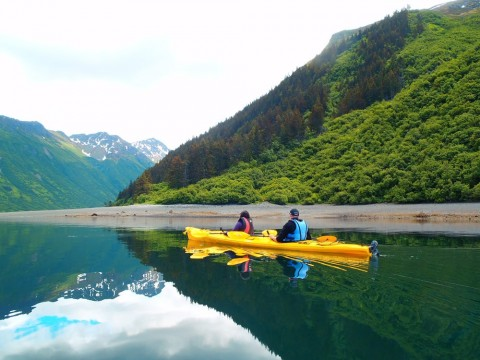 Two people in a yellow kayak glide on the water surrounded by lush mountains.