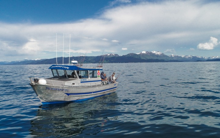 A small fishing boat on the water with mountains in the background.