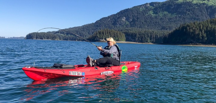 A woman fishes from a kayak.