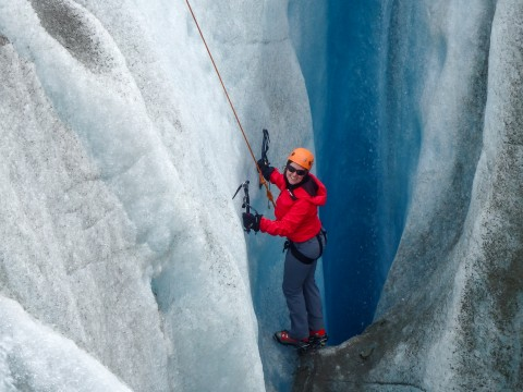 Woman in a red coat ice climbing on Root Glacier.