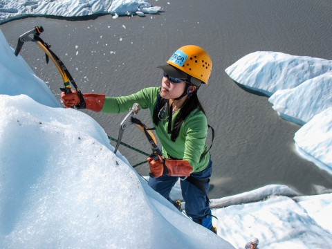 A woman ice climbs up the side of a glacier.