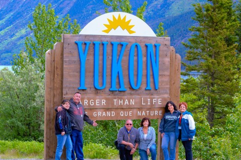 "A group poses in front of a large sign that says ""Yukon""."
