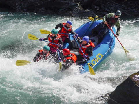 People in an inflatable raft race down a whitewater river.