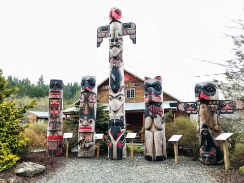 Totem poles displayed in a courtyard.