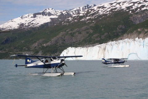 Two float planes on the water with a glacier and mountains in the background.