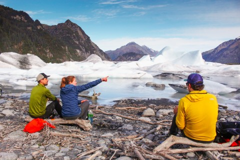 Hikers sit on a rocky beach admiring an ice-choked lagoon.