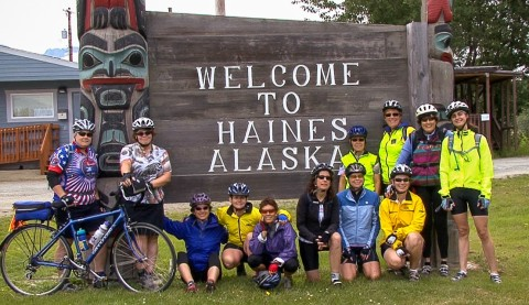 """A group of people in cycling gear pose in front of a large wooden sign that says """"Welcome to Haines Alaska""""."""