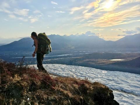 Two backpackers trek through a mountain pass.