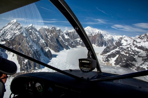 View from the cockpit of a bush plane of snow covered mountains.