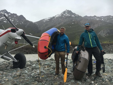 Two men carry packrafts from a floatplane to explore Alaska's national parks