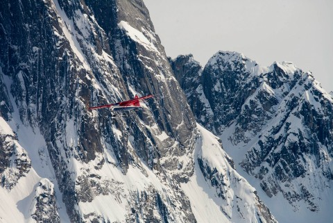 A red bush plane flies close to the face of snow covered Denali.