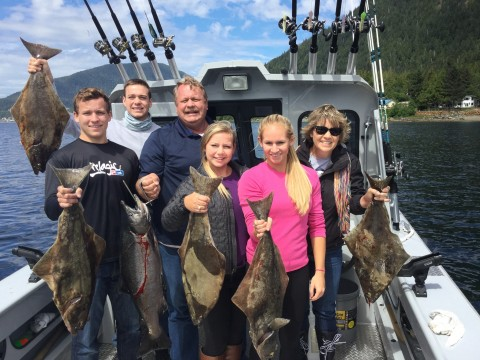 A family aboard a fishing boat hold up the fish they caught.