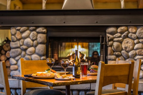 A restaurant table in front of a fire place set with food and wine.