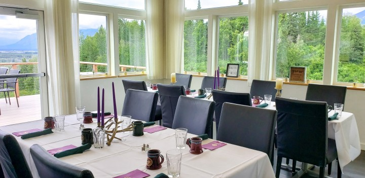 Dining room of Raven's Perch Restaurant with large windows letting in lots of natural light.
