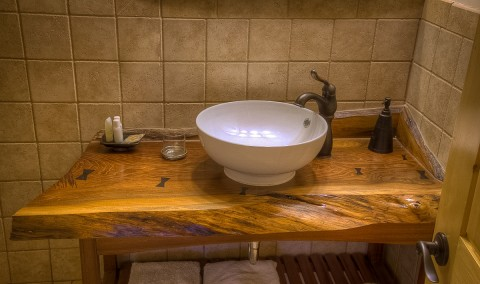 A bathroom sink with a wooden counter top.