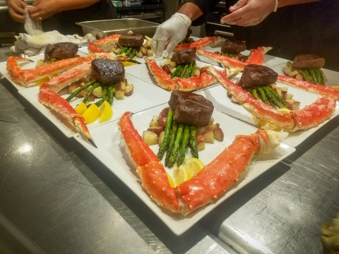 A cook arranges plates of surf and turf with vegetables.