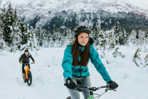 Two people bike through the snow on fat tire bikes.