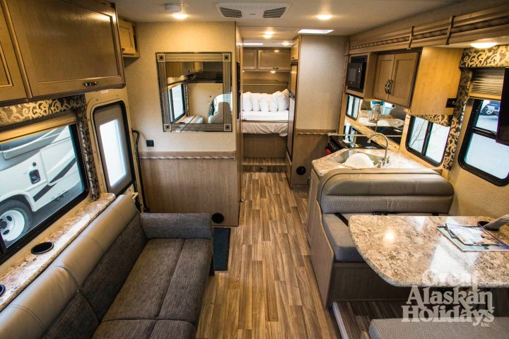 Inside of an RV showing the living area, kitchen, and sleeping area.