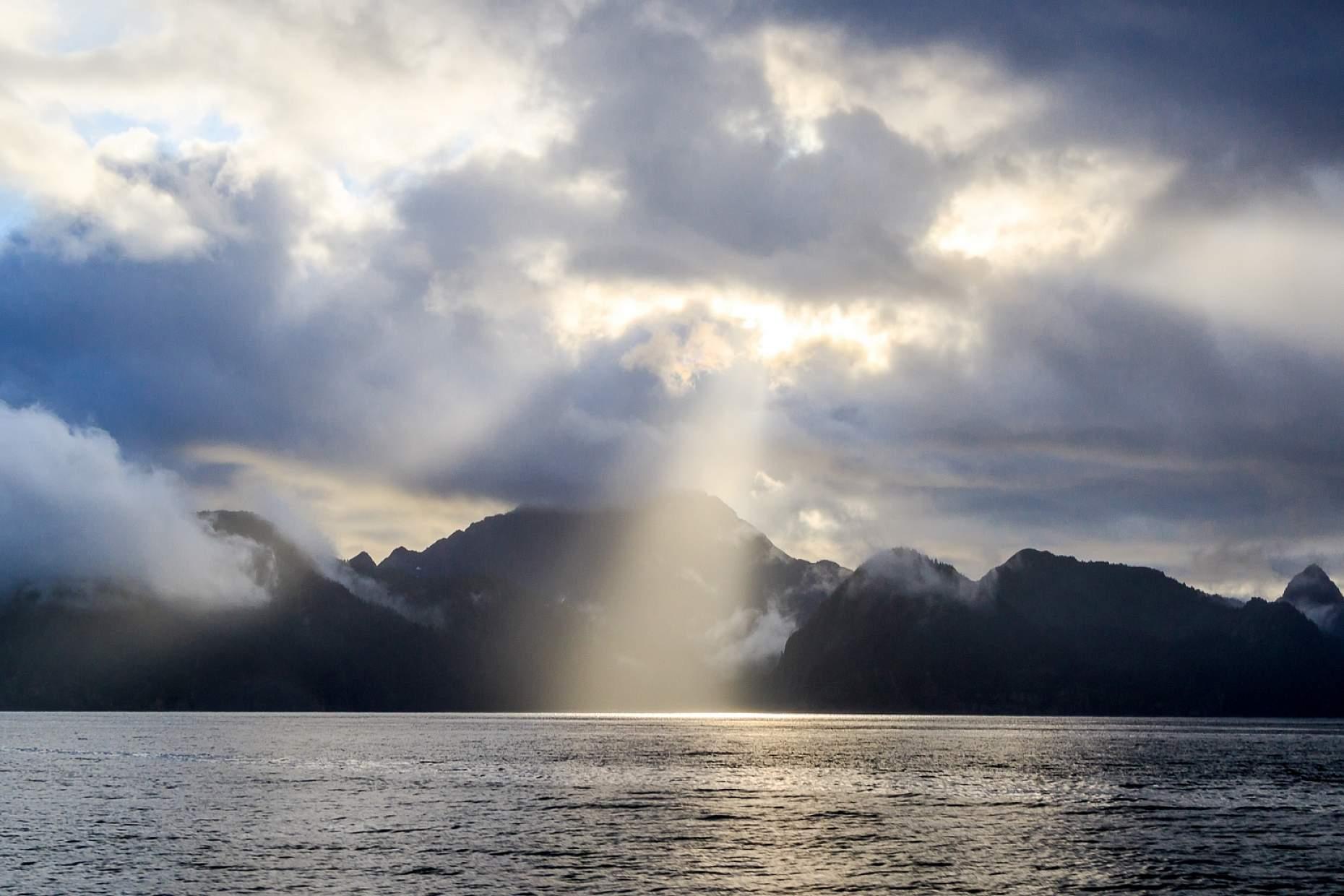 Sun peaks through the clouds in Kenai Fjords National Park