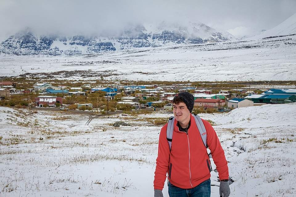 Alexyn Scheller in Gates of the Arctic National Park with the village of Anaktuvuk Pass behind him