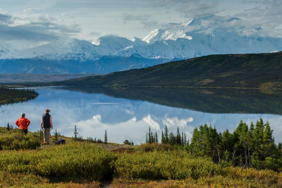 Husband and wife stand in front of Wonder Lake, with Mt. Denali reflecting in the water