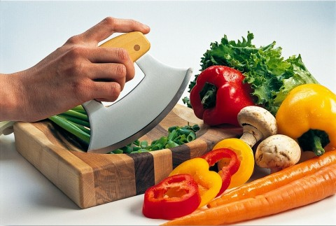An Ulu knife and cutting board surrounded by fresh vegetables