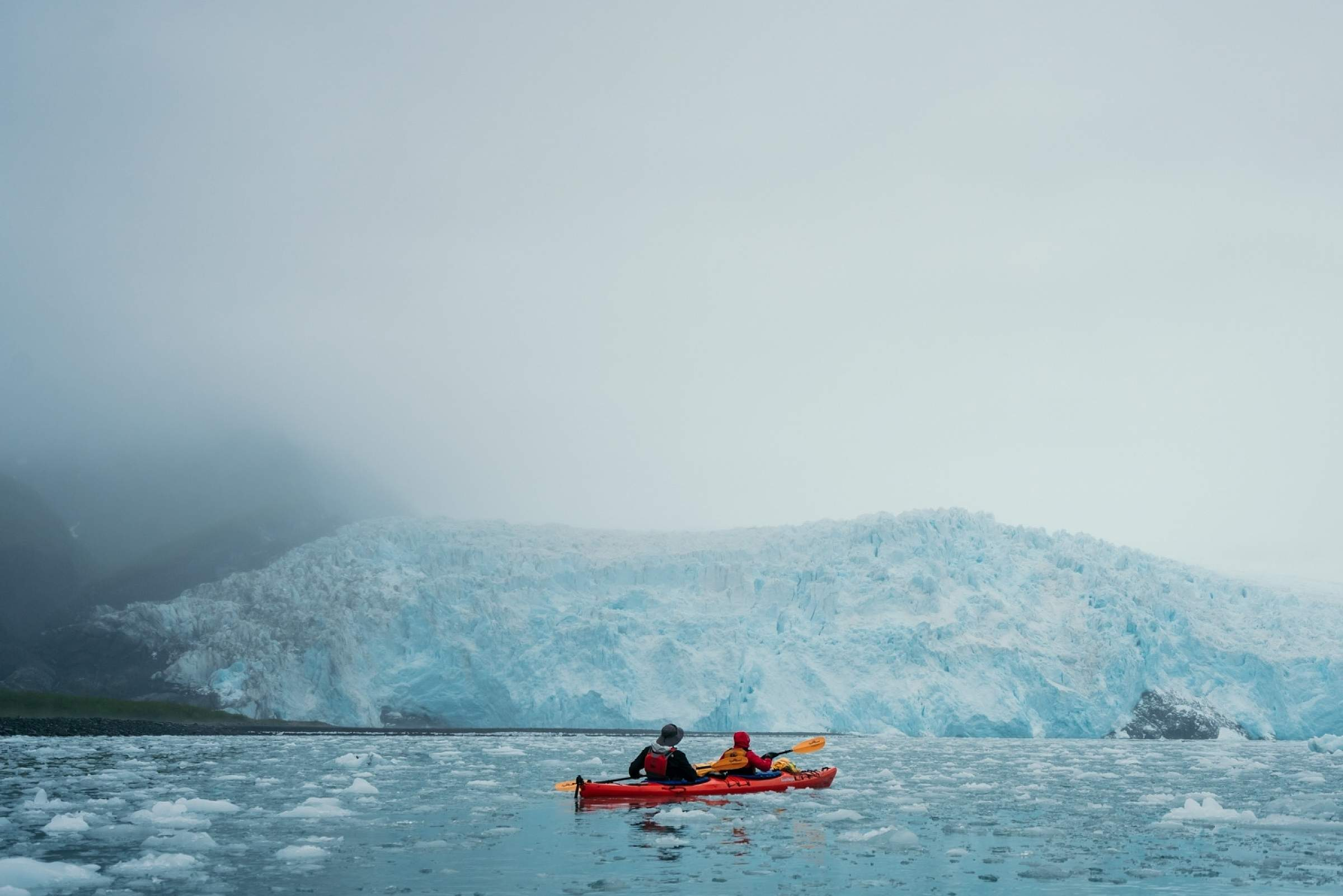 Kayakers pause in front of Aialik Glacier in Kenai Fjords National Park