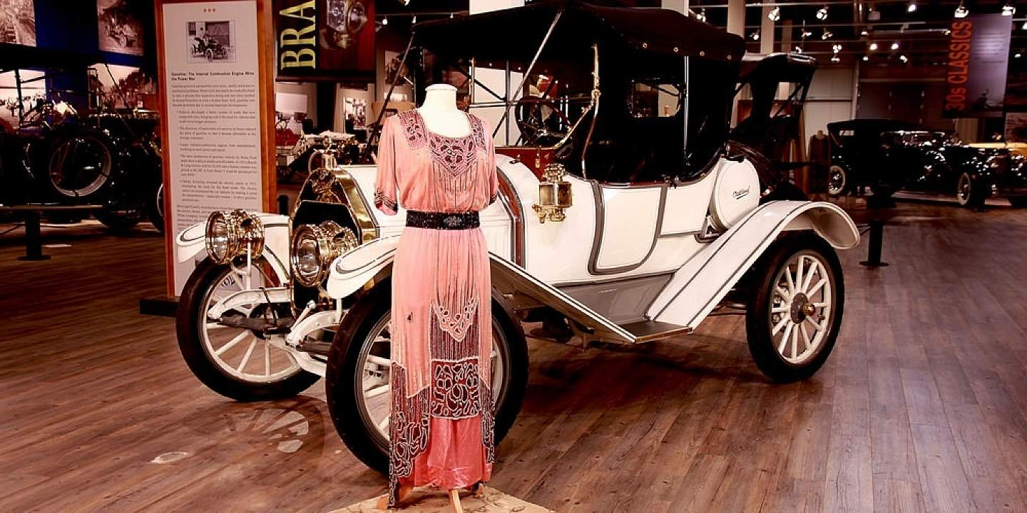 An museum display of a vintage dress and old fashioned car