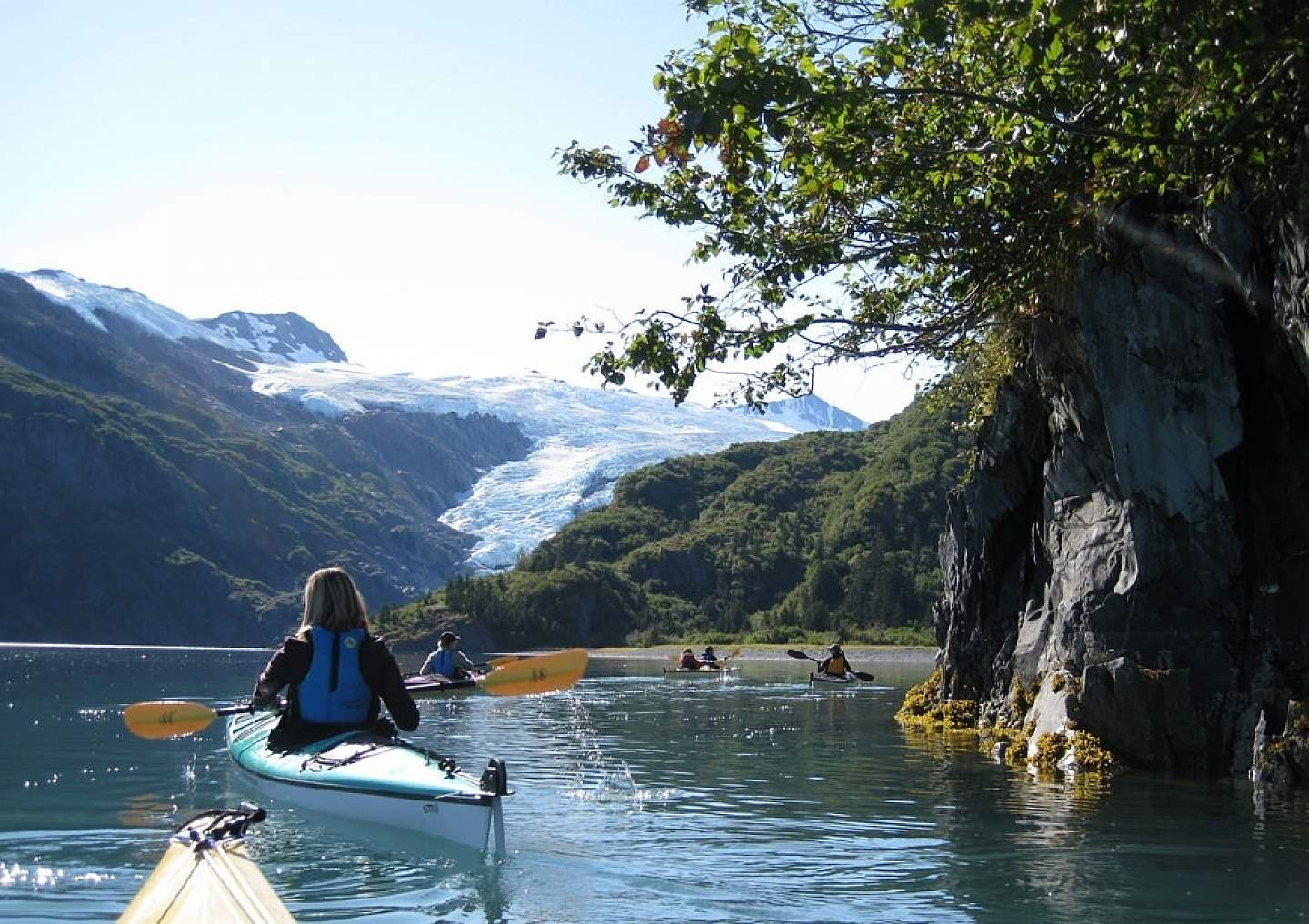 People kayaking in Prince William Sound near a glacier