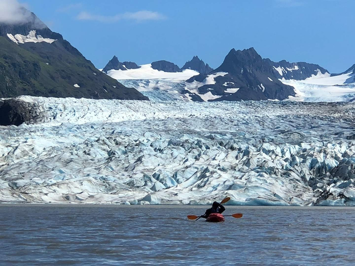 Kayakers on the water close to a glacier