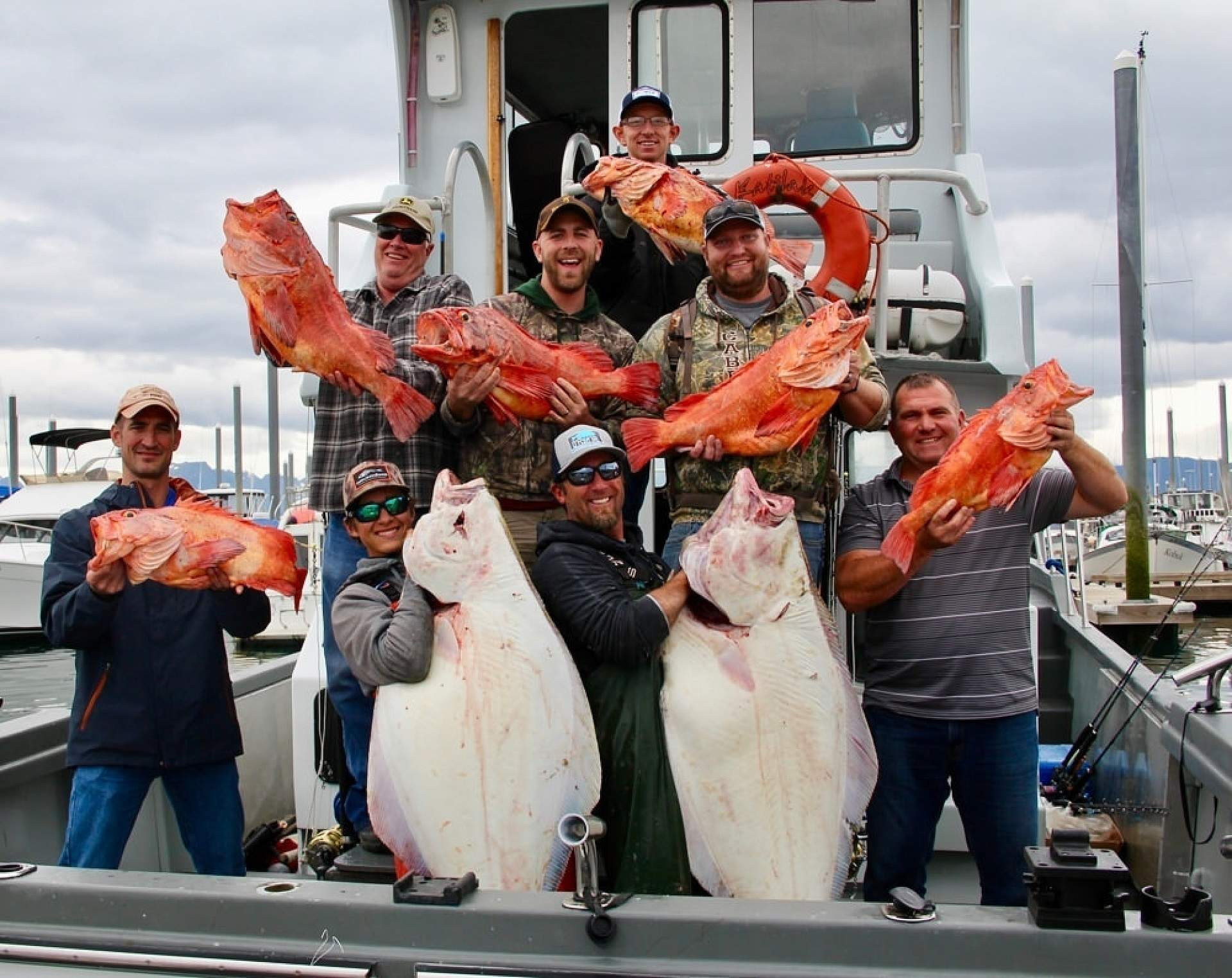 A group of people on a boat hold up fish they've just caught.